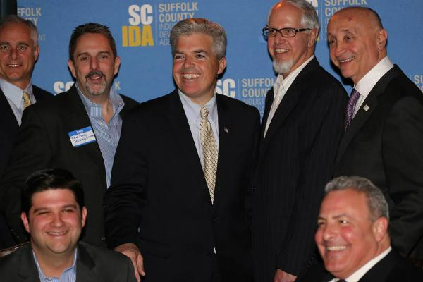 Grant Hendricks, vice chair of the Suffolk IDA, Tyler Roye of Egifter, a web and mobile social gifting app, Suffolk County Executive Steve Bellone, Peter Goldsmith, president of LISTnet, and Tony Giordano, a Suffolk IDA board member. Seated in front are Anthony Manetta, former chairman of the IDA, and Steve Rossetti, IDA board secretary. Photo Credit: Suffolk County.